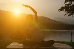 kontur av praktiserande yoga för asiatisk gravid kvinna på gröna gras Arkivbild