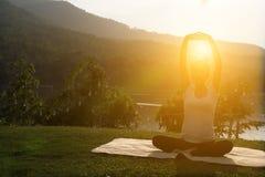 kontur av praktiserande yoga för asiatisk gravid kvinna på gröna gras Royaltyfri Bild