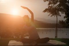 kontur av praktiserande yoga för asiatisk gravid kvinna på gröna gras Arkivfoton