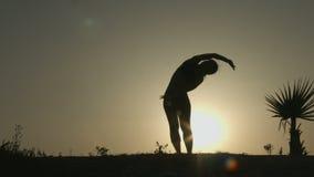 Kontur av praktiserande yoga för kvinna i strålar av soluppgång Jämvikt av kroppen och meningen arkivfilmer