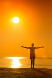 Kontur av praktiserande yoga för kvinna med lyftta armar på solnedgången Arkivbilder