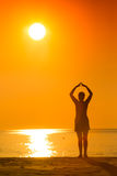 Kontur av praktiserande yoga för kvinna på solnedgången Fotografering för Bildbyråer
