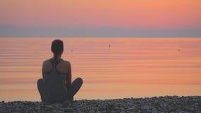 Kontur av praktiserande yoga för ung kvinna nära havet stock video