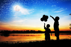 Kontur av punkt för faderbrukshand hans sonblick på fullmånen Royaltyfri Foto