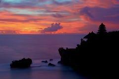 Kontur av Pura Tanah Lot på den färgade solnedgången Arkivbilder