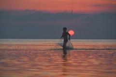 Kontur av pysen mot havet och solnedgången Arkivfoto