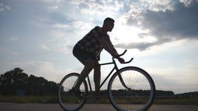 Kontur av ridningen för ung man på tappningcykeln med härlig solnedgånghimmel på bakgrund Sportig grabb som cyklar i arkivfilmer