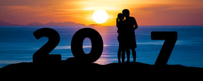 Kontur av romantiker en parkram som kysser mot sommarhavsstranden i solnedgångskymninghimmel, medan fira det lyckliga nya året 20 Arkivbild