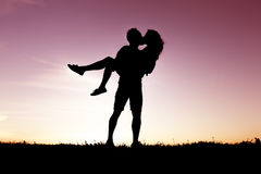 Kontur av romantiska vänner med solnedgång på baksidan arkivbild