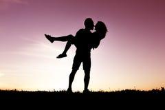 Kontur av romantiska vänner med solnedgång på baksidan royaltyfri foto