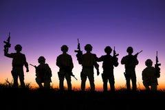 Kontur av soldatlaget med soluppgångbakgrund Arkivbild