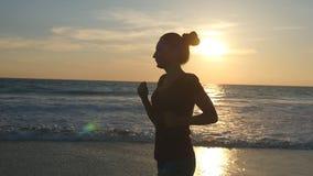 Kontur av spring för ung kvinna på havsstranden på solnedgången Flicka som joggar längs havkust under soluppgång kvinnlig lager videofilmer