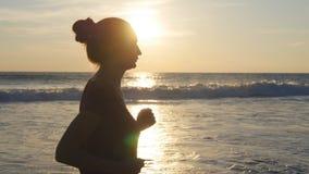 Kontur av spring för ung kvinna på havsstranden på solnedgången Flicka som joggar längs havkust under soluppgång kvinnlig stock video