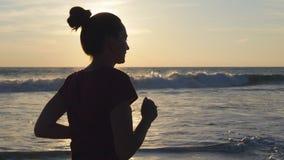 Kontur av spring för ung kvinna på havsstranden på solnedgången Flicka som joggar längs havkust under soluppgång kvinnlig Royaltyfri Fotografi