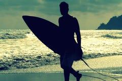 Kontur av surfaren med ett bräde på en solnedgångafton i Manuels Antonios nationalpark Costa Rica Royaltyfri Fotografi
