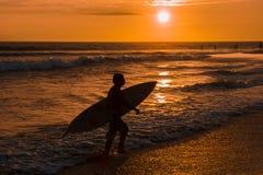Kontur av surfaren med surfingbrädan som går på stranden i solnedgång Fotografering för Bildbyråer