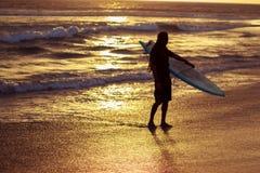 Kontur av surfaren med surfingbrädan som går på stranden i solnedgång Arkivbilder