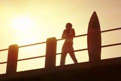 Kontur av surfaren på pir på soluppgång med surfingbrädan Royaltyfri Foto
