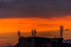 Kontur av telefonantennen med solnedgånghimmel Royaltyfri Bild