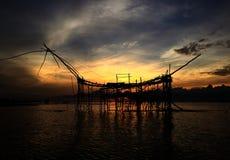 Kontur av traditionellt fiske för gammal kultur på sjön vid träfyrkantigt netto för dopp i soluppgången av morgontid royaltyfria bilder