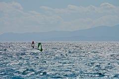 Kontur av två personer som vindsurfar i mitt av havet Royaltyfri Fotografi