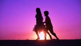 Kontur av två ungar som runniing på solnedgången stock video