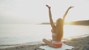 Kontur av ung flickaleken med hennes hår på solnedgången i ultrarapid Aftonmeditationen, kvinna öva yoga på kusten