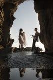 Kontur av unga härliga brud- par som har gyckel tillsammans på stranden Arkivbild