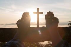 Kontur av unga mänskliga händer som ber med ett kors på soluppgång, Christian Religion begreppsbakgrund arkivbild
