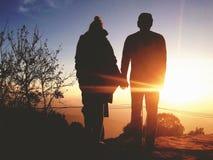 Kontur av unga romantiska parinnehavhänder på den fantastiska guld- solnedgången Bekymmerslöst loppLyfestyle förhållande Royaltyfria Bilder