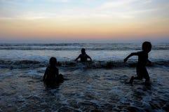 Kontur av unga ungar som spelar på stranden under solnedgång Royaltyfri Bild
