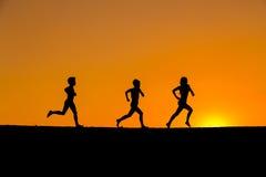 Kontur av ungar som kör mot solnedgång arkivbilder