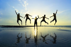 Kontur av vänner som hoppar över solen Royaltyfri Bild