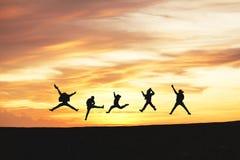 Kontur av vänner som hoppar i solnedgång och moln på kullen med kopieringsutrymme, affär royaltyfri foto