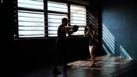 Kontur av vit kvinnlig boxareutbildning för passform med boxninglagledaren på idrottshallen lager videofilmer