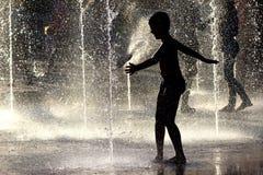 Kontur chłopiec bawić się w fontannie Zdjęcia Stock