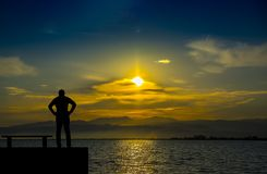 Kontur ensam man som håller ögonen på havet på solnedgången Arkivbilder