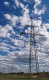 Kontur för elektricitetsöverföringspylon mot blå himmel på skymning royaltyfri bild