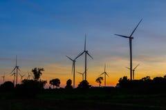 Kontur för vindturbiner på solnedgången Arkivfoto