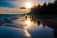 Kontur grupp människor som tycker om solnedgången på stranden arkivbild