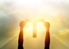 Kontur korset i händer, religionsymbol i ljus och landskap royaltyfri bild