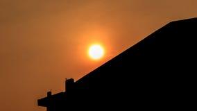 Kontur på solnedgången med byggnad Arkivbild