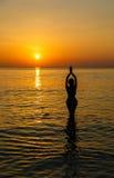 Kontur till den härliga flickan på solnedgången Arkivbilder