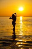 Kontur till den härliga flickan på solnedgången Arkivfoton