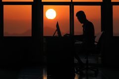 Konturaffärsman som arbetar på en dator med solnedgång Arkivfoto