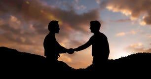 Konturaffärspartners som skakar händer på berg under solnedgång fotografering för bildbyråer