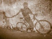 Konturbakgrund, skugga av två cyklistinnehavhänder royaltyfria bilder