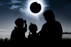 Konturbaksidasikt av familjen som ser sol- förmörkelse på mörker royaltyfri fotografi