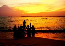 Konturbild av unga turister i solnedgångplats på stranden Arkivbilder