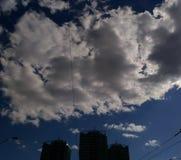 Konturbyggnadsarkitektur i cityscape med det enorma vita molnet på himlen arkivfoto
